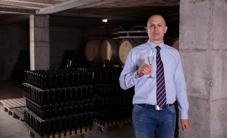 Confident winemaker offering glass of white sparkling wine for tasting in wine cellar Foto de archivo
