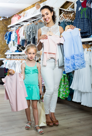 portrait of russian glad woman and girl shopping kids apparel in clothes store