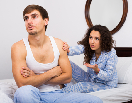 Stressed man sitting apart in bed during quarrel with wife 版權商用圖片