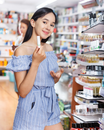 Smiling young girl testing new lipstick in cosmetics shop Stock Photo