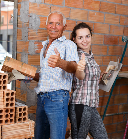 Happy young woman and confident senior man standing with tools and materials in hands in their repairable house