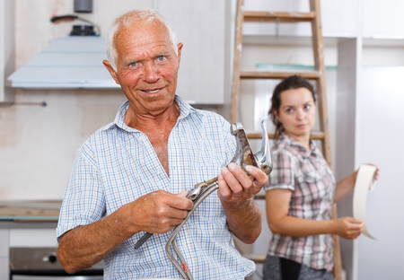 Skillful elderly man preparing faucet for installation during repairs in his apartment
