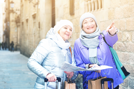 Two positive elderly women tourists with city guide walking on street