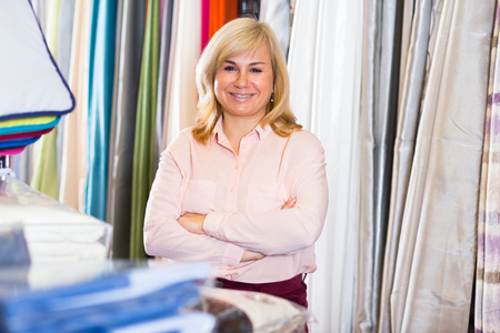 Positive mature woman standing among shelf in the textile shop Standard-Bild