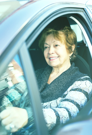 Attractive mature woman sitting in new car at driver seat
