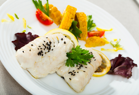 Hake fillet steamed in pan with water and olive oil for 10 minutes, seasoned with salt and pepper, garnished with boiled corn, greens, lemon