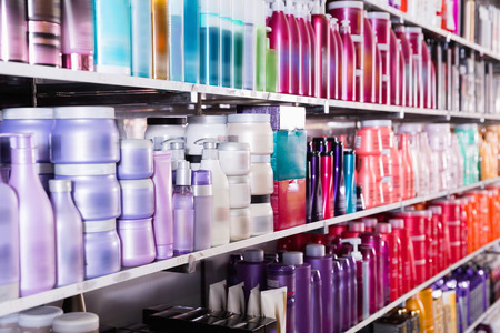 Image of shelves with fashionable modern beautiful stylish conditioners and mousses for hair in the store. 스톡 콘텐츠