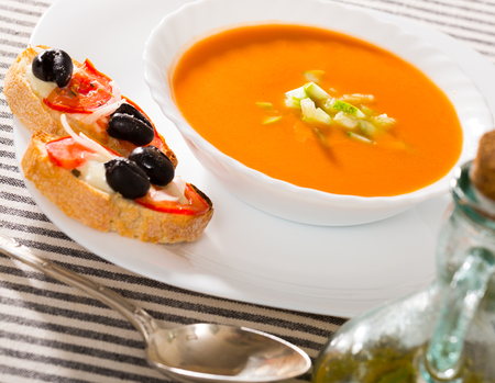 Traditional Spanish cold gazpacho soup served with toasts with creamy sauce, tomatoes and black olives Stockfoto
