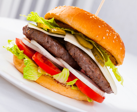 Tasty double-decker  grilled burger with beef, tomato, cheese, cucumber and lettuce