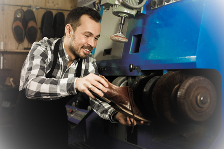 Positive adult worker repairing shoe in specialized workshop Standard-Bild