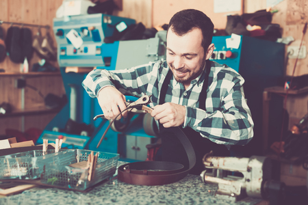 Man worker working at forming hole in belt in repair workshop
