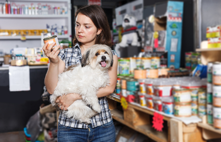 Young serious woman with dog  buying  preserves for dogs in pet shop Standard-Bild