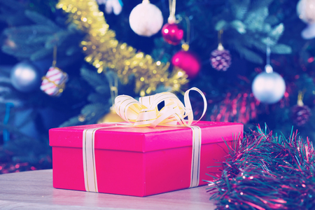Red gift box with gold ribbon on blurry background with decorated Christmas tree