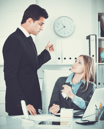 Businessman feeling angry to female coworker at workplace in office