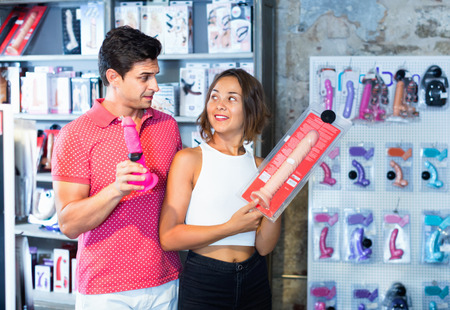 Glad  smiling male and female purchasers touching big dildo in the modern sex shop