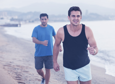 Two friends are jogging in time training on the beach near sea. Imagens