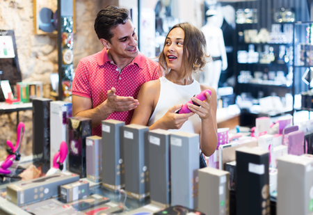 positive british female and male purchasers touching in the modern sex shop different sexy toys