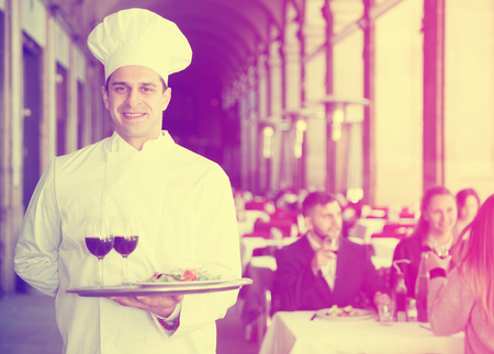 Portrait of professional chef with serving tray meeting restaurant guests Archivio Fotografico