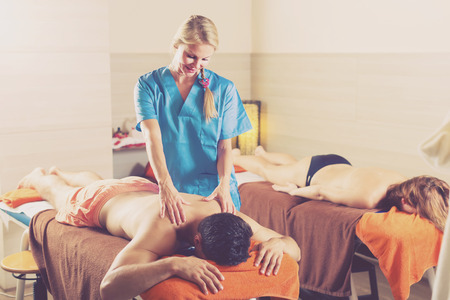 Woman masseuse is doing massage for couple in spa-salon. Stock Photo