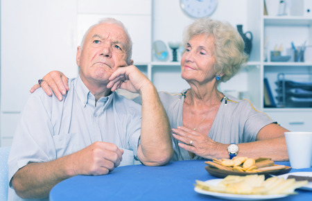 Senior woman asking for forgiveness from her offended husband sitting separately