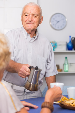 Gallant senior man pouring coffee to his female guest at home