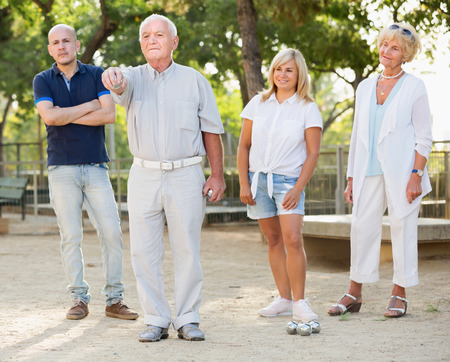 Mature man with friends playing petanque in park outdoor Stock Photo