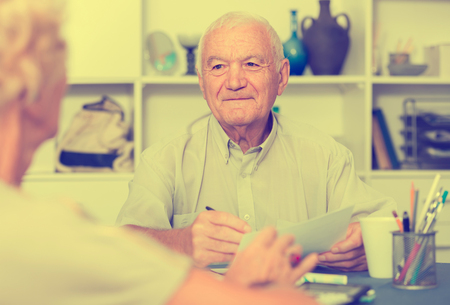 Smiling senior man sitting at home table discussing with wife their bills