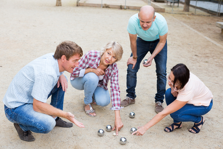 Smiling mature people playing petanque on sand together