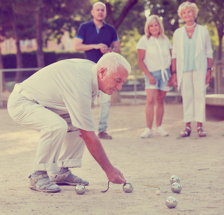 Happy family of two generations playing bocce in a garden Stock Photo