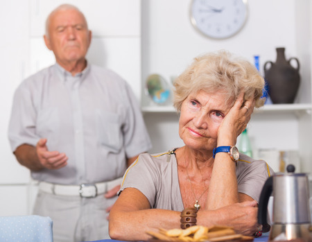 Upset mature woman dont speaking after discord with man standing behind