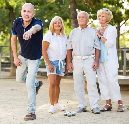 Happy senior people playing bocce in the park Stock Photo