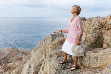 Portrait of mature woman wearing casual clothes relaxing at seaside Фото со стока - 106084722