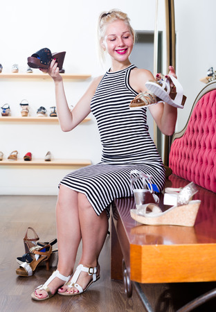 Glad girl trying on pair of sandals in shoe store Stock Photo