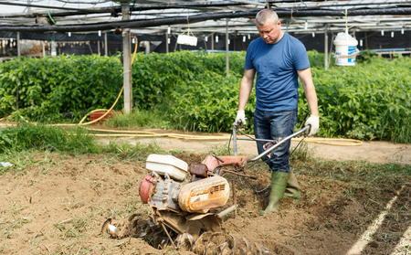Male farmer cultivating land with hand motor plow to prepare for planting in greenhouse