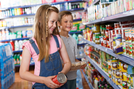 Smiling girl and boy choosing preserved meal for home in the supermarket