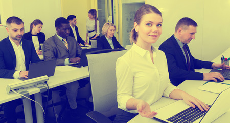 Portrait of young smiling business woman with coworkers during daily work in modern office Stock Photo