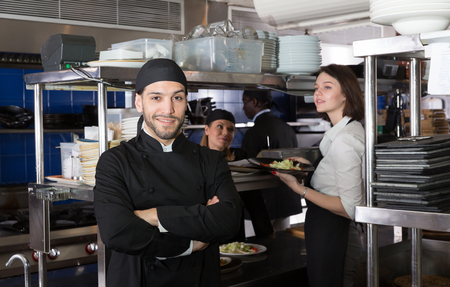 Portrait of handsome bearded chef standing in kitchen of restaurant with working staff Standard-Bild