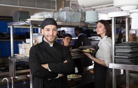 Portrait of handsome bearded chef standing in kitchen of restaurant with working staff Foto de archivo