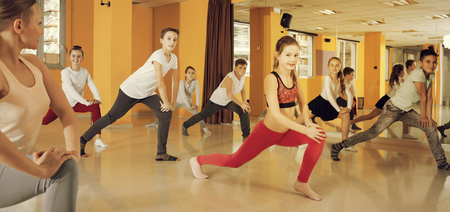 Group of tweens exercising with female coach in choreography class