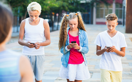 Three  cheerful  children keened on mobile phones during joint walk around city Imagens