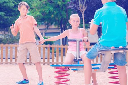 Cheerful children are teetering on the swing on the playground. Standard-Bild