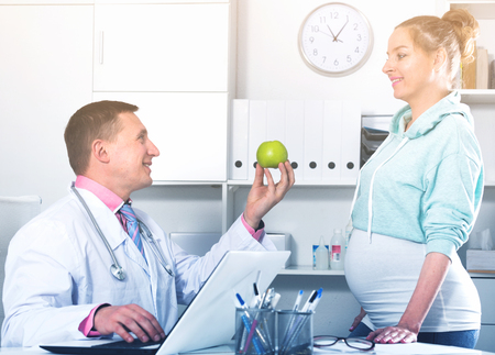 Middle-aged pregnant woman having consultation with male doctor in hospital