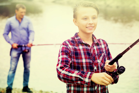 Happy teenager boy fishing using rod from water side on river