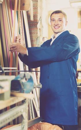 portrait of smiling russian man in uniform choosing framing moulding in studio Foto de archivo