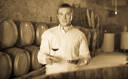 positive man posing with glass of wine in winery cellar