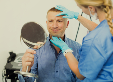 Female doctor is preparing client to procedure in cabinet. Stock Photo