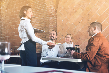 Pleasant cheerful positive female waiter bringing order to visitors in country restaurant