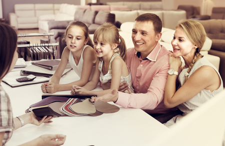Man with wife and kids are consulting with the seller about the color of sofa.