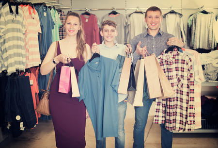 Positive woman, man and boy displaying shopping bags with purchase in store. Focus on man