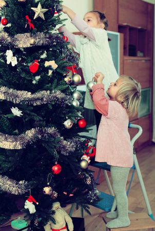 Two little sisters decorating Christmas tree at home. Selective focus on one girl Banque d'images